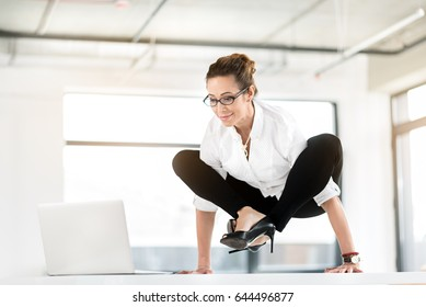 I cannot sit comfortably. Female demonstrating happiness while working with laptop in lotus position. Uncomfort concept