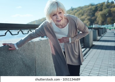 Cannot stand this pain. Scared elderly woman feeling intense physical discomfort and holding her hand at abdominal area while walking along the riverwalk.