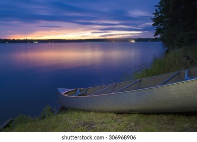 Canoe beached on north woods forest shoreline along glassy lake at sunset
