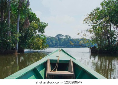 A canoe boat on the brown amazon river. The warm tropical sun shines high over the water with the dense amazon rainforest in the background. In the boats are travelers on vacation on an adventure.