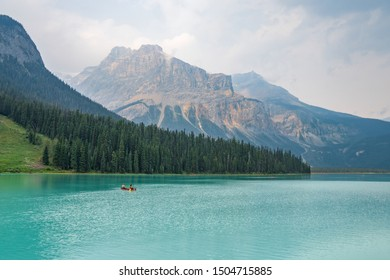 Canoe drifting in still crystal clean waters in Canada. Landscape panorama of valley with mountains and trees wood. People doing recreational water sports activities and spending time outdoors.