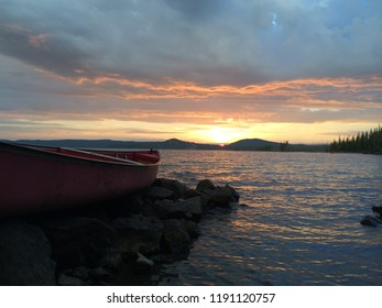Canoe in foreground and sunset sky in background at Waldo Lake in Oregon