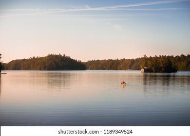 Canoe on tranquil Lake Joseph, Muskoka, at sunrise