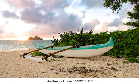 A canoe rests on a tropical beach during sunset in Oahu, Hawaii