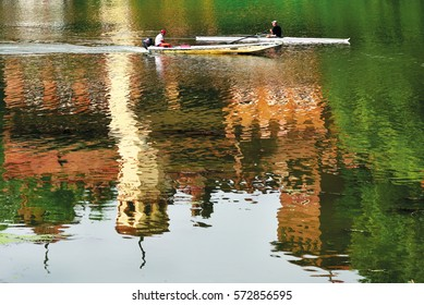 A canoe sails the waters of the River Po in front of the medieval village and castle of the Valentino in Turin