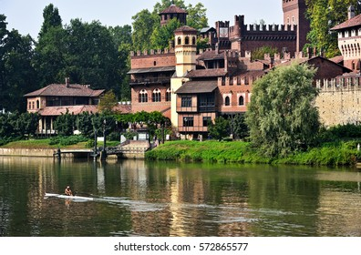 A canoe sails the waters of the River Po in front of the medieval village and castle of the Valentino in Turin, Italy