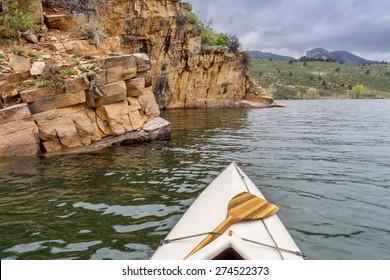 canoe and sandstone cliff - springtime paddling Horsetooth Reservoir near Fort Collins, Colorado
