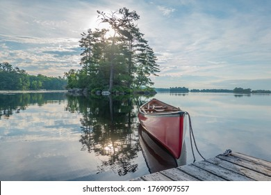 Canoe tied to a dock on the calm waters of Stony Lake in the morning,
