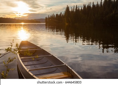 Canoe tied to shore of beautiful Frenchman Lake in remote wilderness of Yukon Territory, Canada, with sunset over boreal forest taiga framing the lake