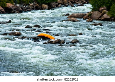 """canoe upside down in middle of river conceptualizing """"up the creek with out a paddle"""""""