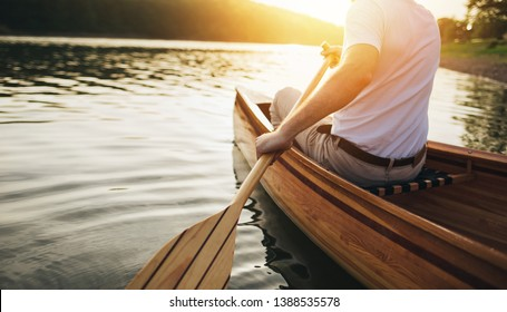 Canoeing. Close up of man holding canoe paddle at sunset lake