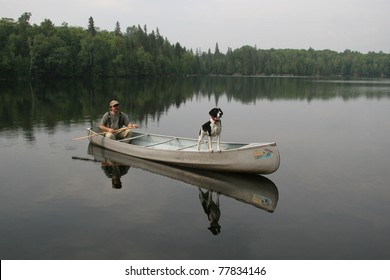 Canoeist and Dog with Reflection on a Lake  in Northern Ontario, Canada