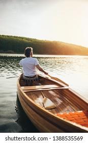 Canoeist paddling the wooden boat with oar.