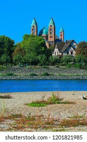 Canoeists on the river Rhine in front of the impressive appearance of the largest surviving Romanesque church in the world, the Speyer Cathedral