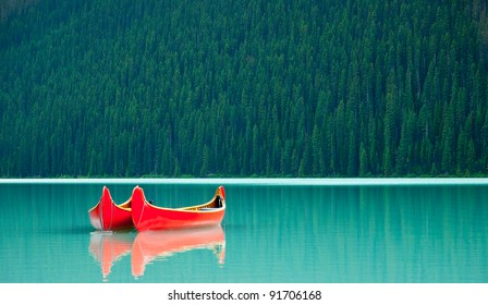Canoes floating peacefully on the waters of Lake Louise, Banff National Park, Alberta, Canada.