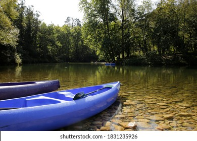 canoes or kayaks on the bank of a beautiful river with a background of trees and kayaks descending the river. sport and nature context. Sella river, Spain