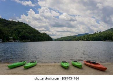 Canoes and Kayaks resting on the beach of Lake Lure in North Carolina.