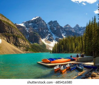 Canoes on a jetty at  Moraine lake in Banff National Park, Alberta, Canada, with snow-covered peaks of canadian Rocky Mountains in the background.