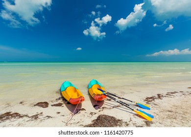 Canoes on pristine sunny tropical beach in Mexico