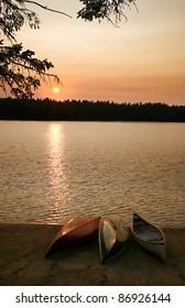 Canoes on shore on lake at sunset/sunrise