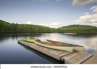 Canoes on a wooden dock in Muskoka Cottage country