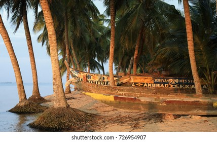Canoes and palm trees in the coastal town Ada Foah, Ghana