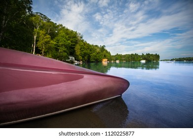 Canoes rests on a sandy shore of a calm blue lake in the Muskoka region in Ontario, Canada
