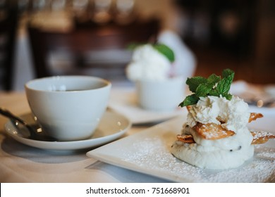 Canoli cream and waffer dessert with whip cream and mint sitting on table with white table cloth in fine dining restaurant with window light. Film grain look