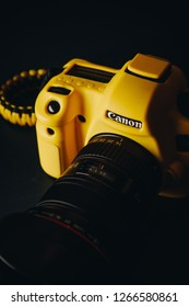Canon 6D with 16-35 f/2.8 lens on it. Camera covered in yellow EasyCover case. Studio shot of a full-frame DSLR camera.