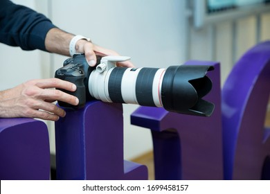 A canon 70-200 L lens close up . The photographer is holding a professional photo Camera Canon EF 70-200mm f 2.8L USM Lens . He puts the camera on a capital letter and takes a video.