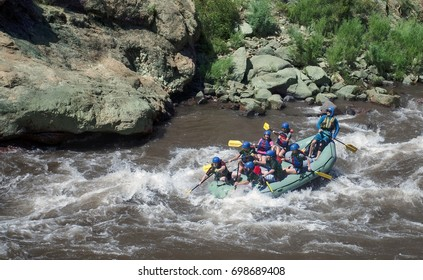 Canon City CO USA, July 18, 2017: Class III-V whitewater challenges even the most experienced rafters, as this boatload of rafters is slammed by the boiling waves of the Arkansas river at Royal Gorge