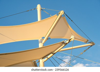 Canopies anchored to steel structures provide shade at an outdoor pavilion.