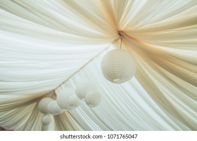 Canopy from fabric of dairy color with the Chinese paper flashlights