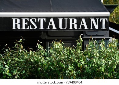 Canopy of restaurant sign with bush