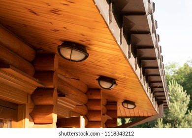 The canopy of the wooden roof of the building made of log house with all-weather street lights