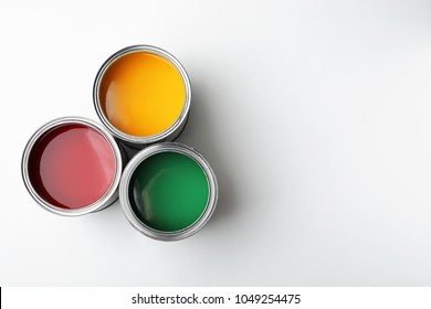 Cans with different decorator's paints on white background, top view