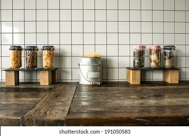 Cans with different grocery items on wooden kitchen table