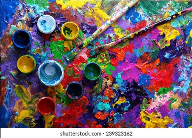 Cans of paint and brush on colorful painted background