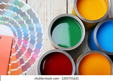 Cans with paint and color palette on wooden background, top view