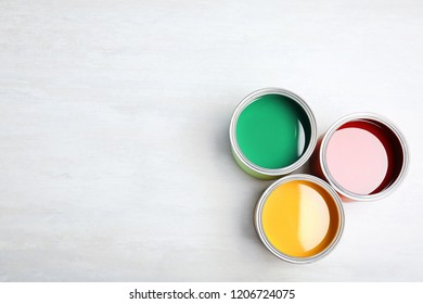 Cans with paint on light background, top view. Space for text