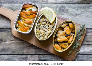 Cans of preserves with clams, cockles and mussels on a rustic table