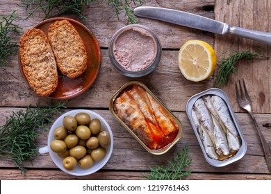 Cans of preserves, olives, foie gras and bread seen from above on rustic wooden table.
