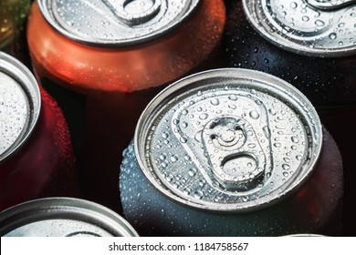 Cans of sweet drinks and beer. Cooling frozen and with water drops