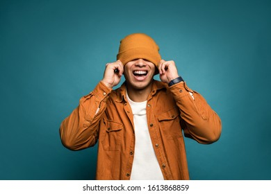 I can't see you! Photo of attractive mixed race man in yellow outfit, wearing hat and glasses smiling in good mood isolated over blue background, pull hat over his head and laugh out loud.