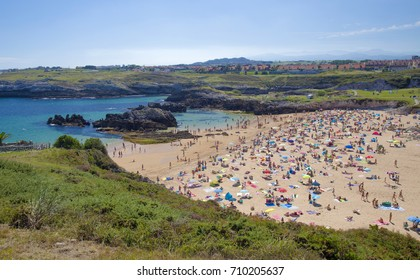 CANTABRIA, SPAIN - AUGUST 12: Locals and tourists enjoy hot Saturday on the beach Playa de San Juan de La Canal, August 12, in Cantabria, Spain