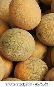 Cantalope in a market is being displayed.