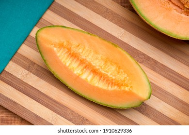 cantaloupe melon sliced on a bamboo chopping board with a green cloth napkin. top view