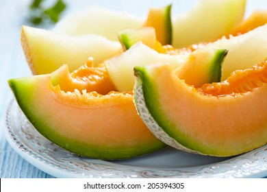 Cantaloupe melon slices on blue wooden table
