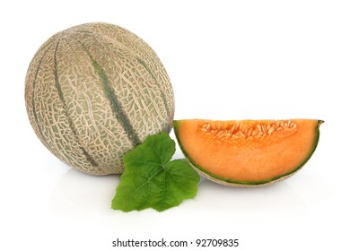 Cantaloupe melon whole and with a slice with leaf sprig isolated over white background.