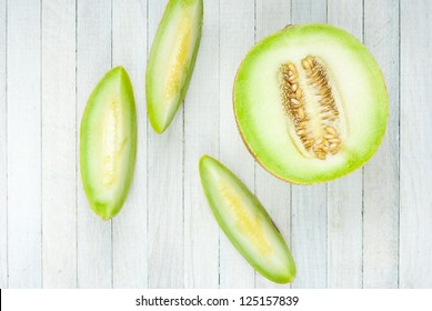 cantaloupe slices on bright wooden table